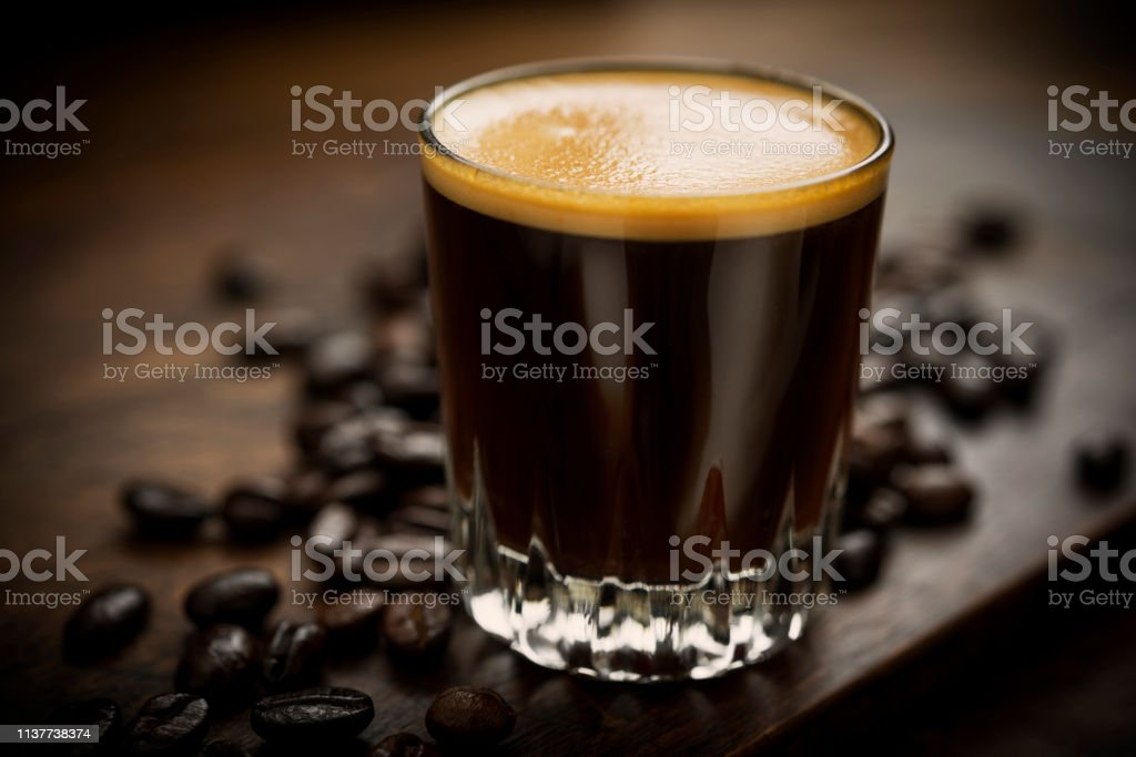 Shot glass with Freshly brewed Espresso Coffee. stock photo