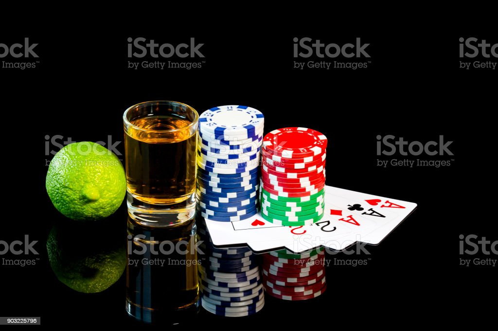 Shot glasse of tequila with poker cards and playing chips stock photo