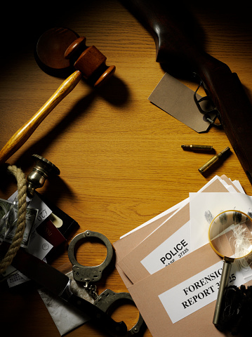 Police handcuffs, shot gun and bullets as evidence, with a gavel and mallet on a desk with a murder case paper file and a magnifying glass. copy space.