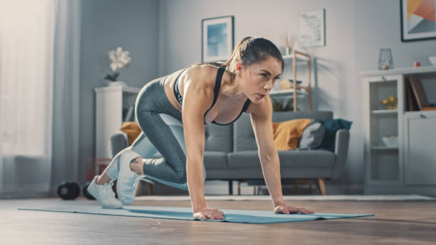 Shot of a Beautiful Confident Strong Fitness Female in a Grey Athletic Outfit is Doing Mountain Climber Exercises in Her Bright and Spacious Apartment with Cozy Minimalistic Interior. – Foto