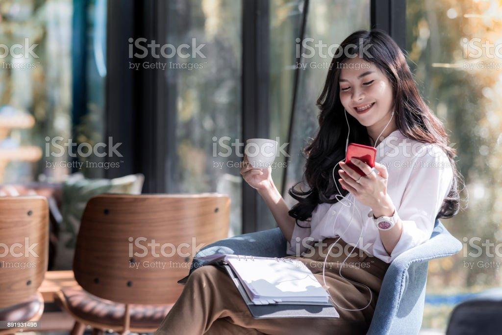 Tiro de una hermosa mujer asiática joven celebración taza de café y escuchar música desde su teléfono en la tienda de café foto de stock libre de derechos
