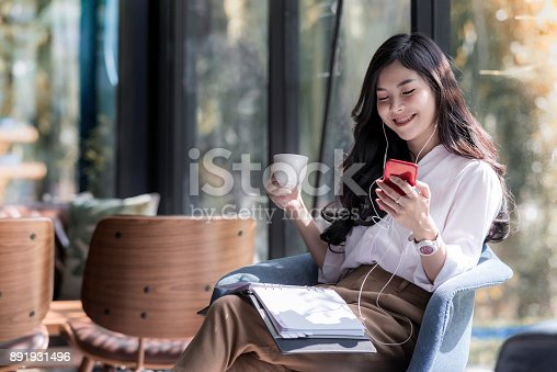 istock Shot of a beautiful young asian woman holding cup of coffee and listening  music from her phone in the coffee shop 891931496