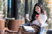コーヒーのコーヒー ショップに彼女の携帯電話から音楽を聴く美しい若いアジア女性保持カップのショット