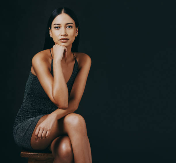 Shot of a beautiful young woman sitting against a black background stock photo