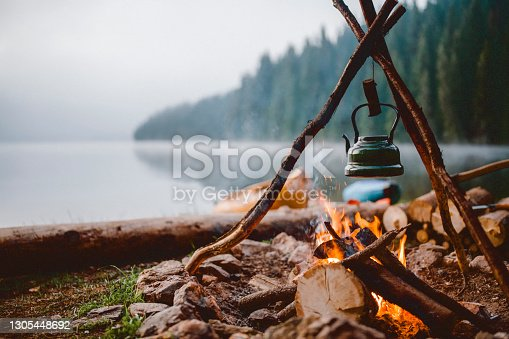 istock Shot of a cute vintage teapot in a campsite near to lake. 1305448692
