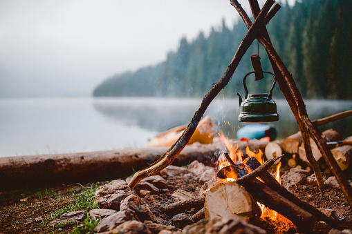 Campfire with a vintage kettle next to the beautiful lake.