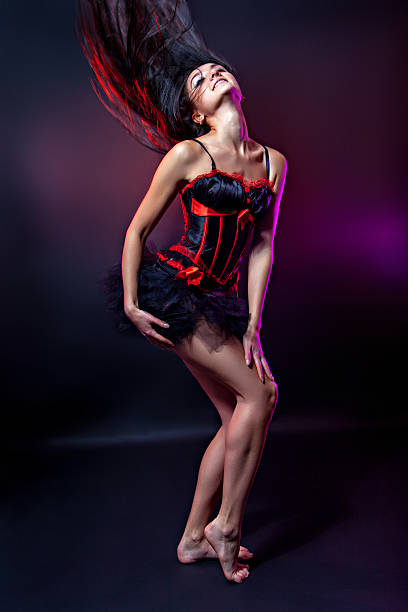 shot of a dancing woman in elegant red-black corset - burlesque stock photos and pictures