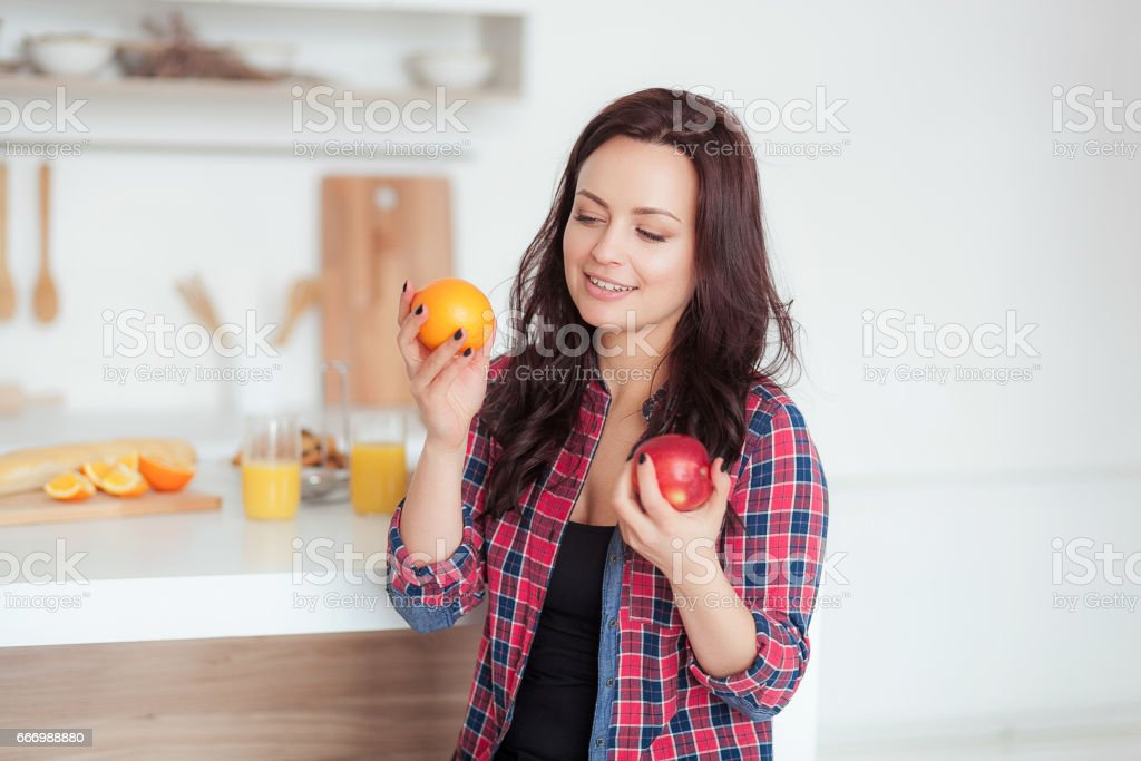 shot of a dark haired caucasian woman comparing apples to oranges stock photo