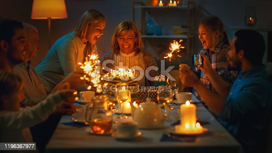 Shot of a Daughter Bringing Birtday Cake with Candlelights to Her Senior Mother. Family Dinner and Celebration, People Gathered at the Evening Dinner Table.