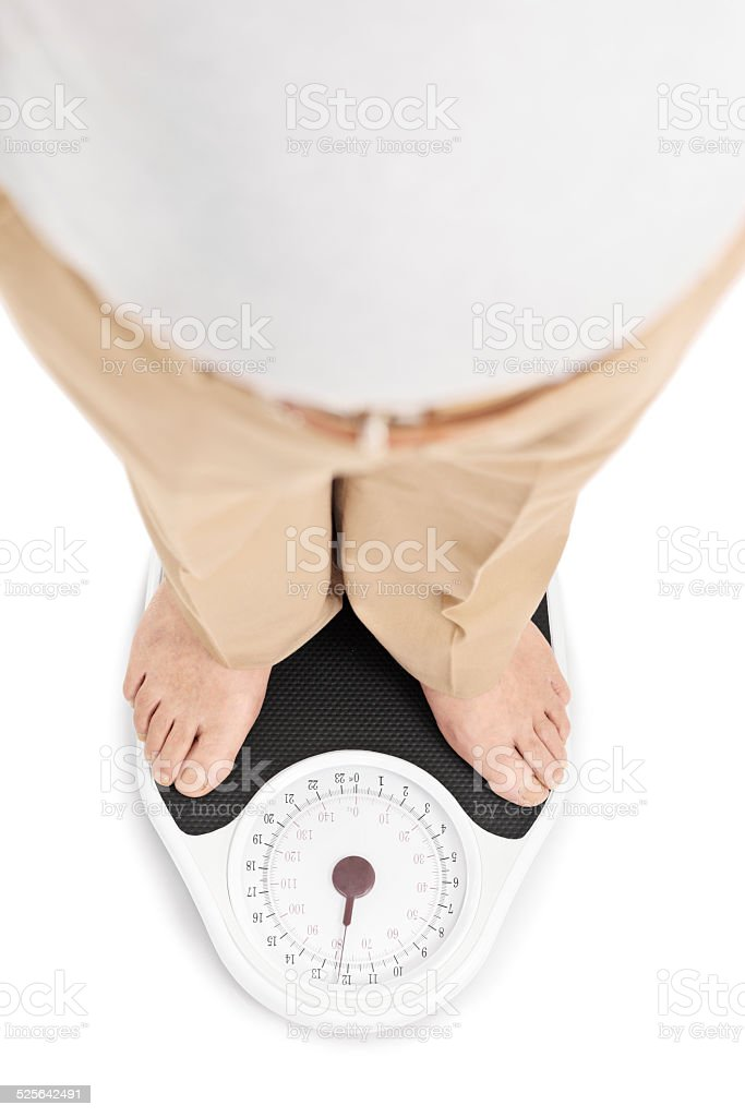 Shot of a man standing on a weight scale stock photo