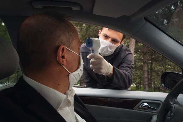 Shot of a security guy measuring a driver's body temperature with thermometer stock photo