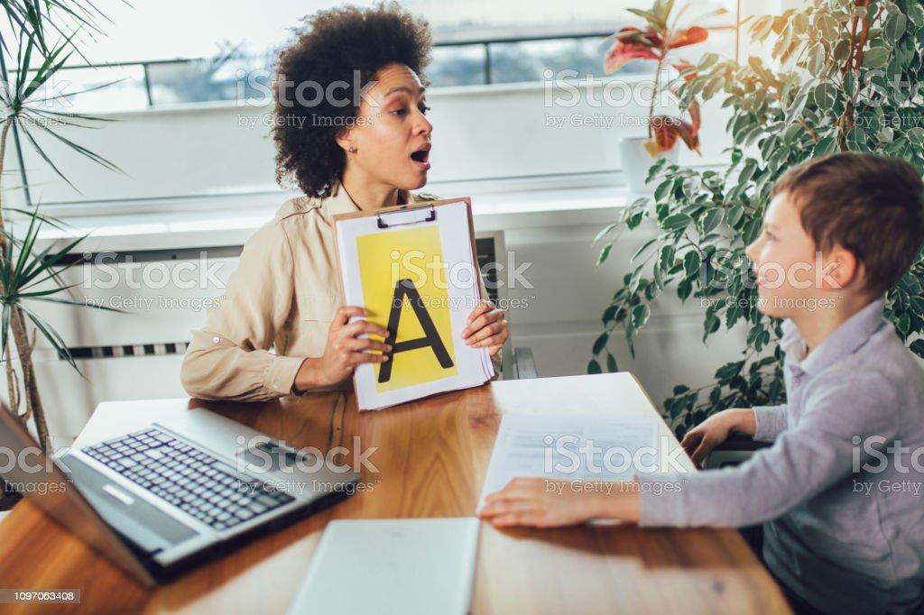 Disparo de un logopeda durante una sesión con un niño pequeño - foto de stock