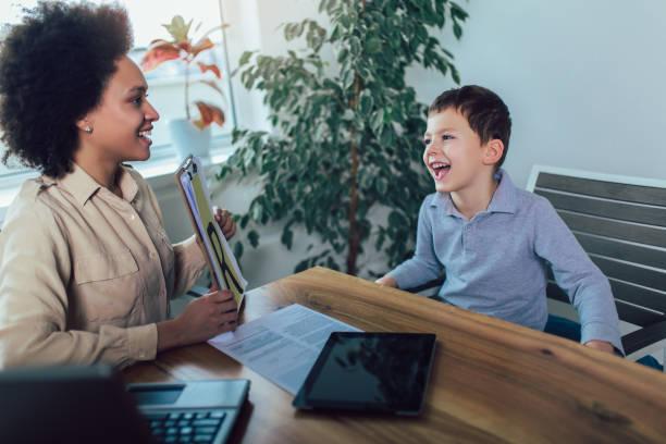 schuss eines sprachtherapeuten während einer sitzung mit einem kleinen jungen - autismus stock-fotos und bilder