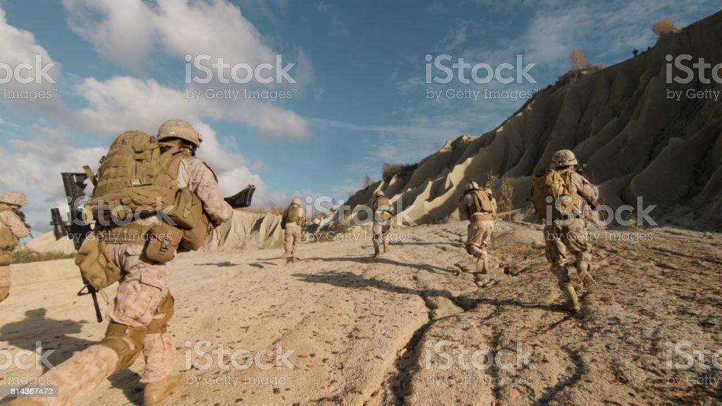 Foto de um pelotão de soldados correndo para a frente e escalando inimigo durante operação militar no deserto. - foto de acervo
