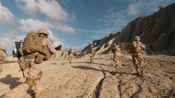 Shot of a Squad of Soldiers Running Forward and Atacking Enemy During Military Operation in the Desert. stock photo