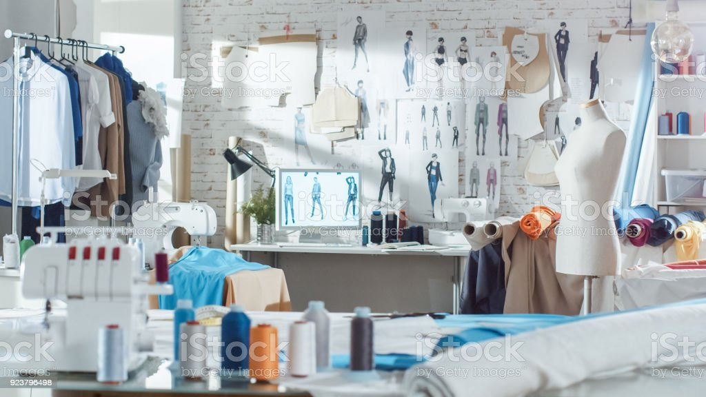 Shot Of A Sunny Fashion Design Studio We See Working Personal Computer Hanging Clothes Sewing Machine And Various Sewing Related Items On The Table Mannequins Standing Colorful Fabrics Stock Photo Download