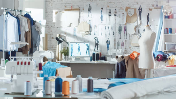 Shot of a Sunny Fashion Design Studio. We See Working Personal Computer, Hanging Clothes, Sewing Machine and Various Sewing Related Items on the Table, Mannequins Standing, Colorful Fabrics. stock photo
