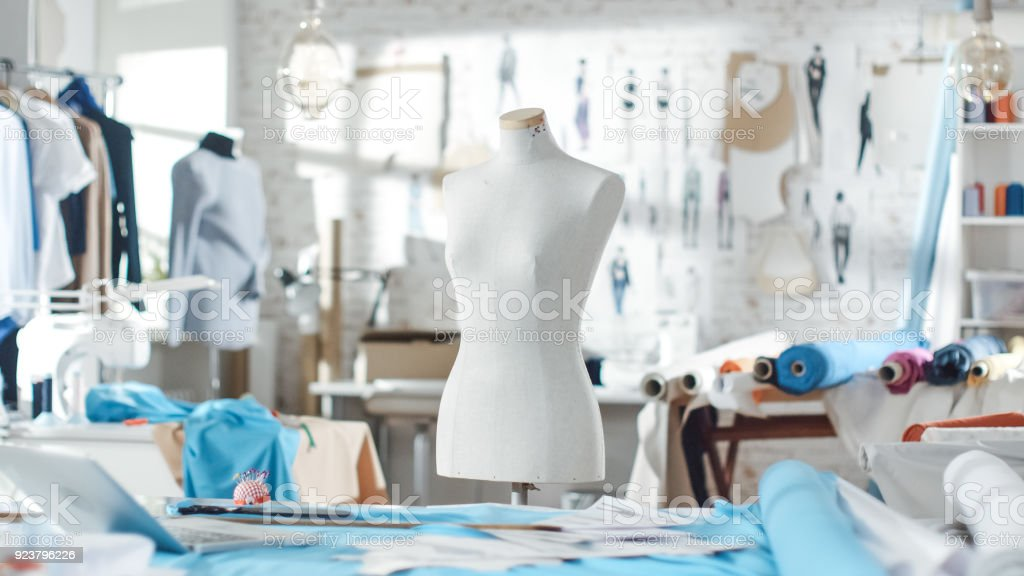 Shot of a Tailoring Mannequin that Stands in a Bright and Sunny Studio. Various Sewing Items and Colorful Fabrics Laying around, Mannequins Standing, and Sketches Pinned to the Wall. stock photo