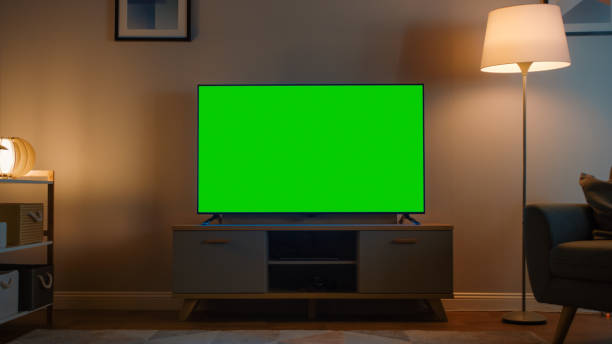 Shot Of A Tv With Horizontal Green Screen Mock Up Cozy Evening Living Room With A Chair And Lamps Turned On At Home Stock Photo Download Image Now Istock