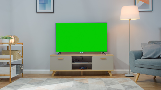 Shot Of A Tv With Horizontal Green Screen Mock Up Cozy Living Room At Day Time With A Chair And Lamps Turned On At Home Stock Photo Download Image Now Istock