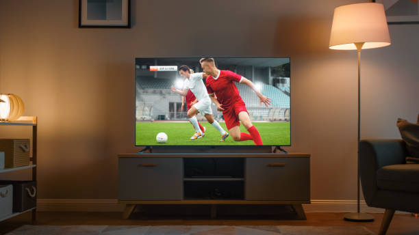 Shot of a TV with Soccer Match. Cozy Evening Living Room with a Chair and Lamps Turned On at Home. stock photo