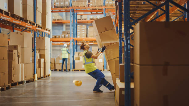 Shot of a Warehouse Worker Has Work Related Accident. He is Falling Down BeforeTrying to Pick Up Heavy Cardboard Box from the Shelf. Hard Injury at Work. stock photo