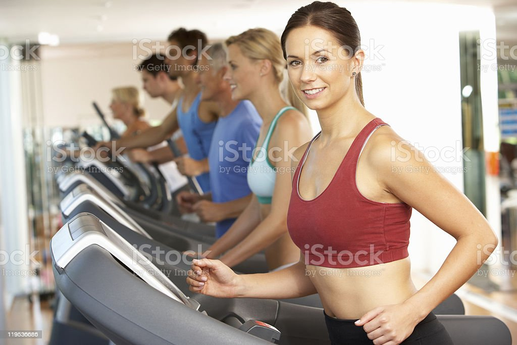 Shot of a woman running on treadmill in a gym with people royalty-free stock photo