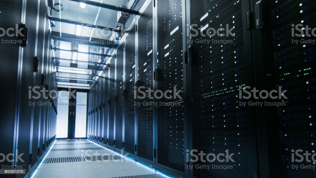 Shot of a Working Data Center With Rows of Rack Servers. People Walk and Work there, they are Blurred in Motion. Long Exposure Shot. stock photo
