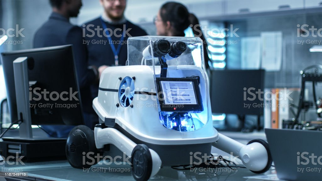 Shot of a Working Robot Prototype in a Modern Laboratory/ Research Center Creating Robotics. Multiethnic Group of Young Scientists have Discussion on backgrounds. Shot of a Working Robot Prototype in a Modern Laboratory/ Research Center Creating Robotics. Multiethnic Group of Young Scientists have Discussion on backgrounds. Adult Stock Photo