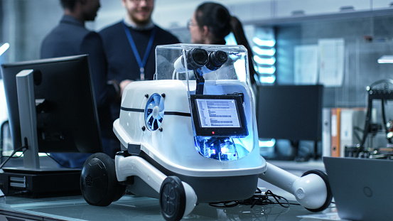 Shot Of A Working Robot Prototype In A Modern Laboratory Research Center Creating Robotics Multiethnic Group Of Young Scientists Have Discussion On Backgrounds Stock Photo - Download Image Now