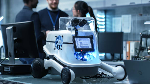 toma de un prototipo de robot de trabajo en un laboratorio moderno / centro de investigación creando robótica. grupo multiétnico de jóvenes científicos tienen discusión sobre los antecedentes. - robótica fotografías e imágenes de stock