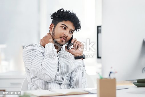 istock Shot of a young businessman looking stressed out while talking on a cellphone in an office 1329681498