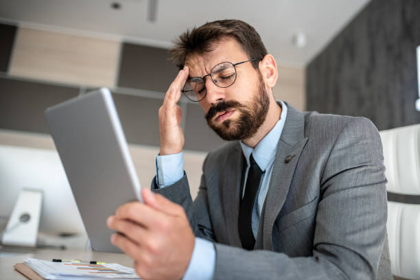 Shot of a young businessman looking stressed out while working on a digital tablet in office stock photo