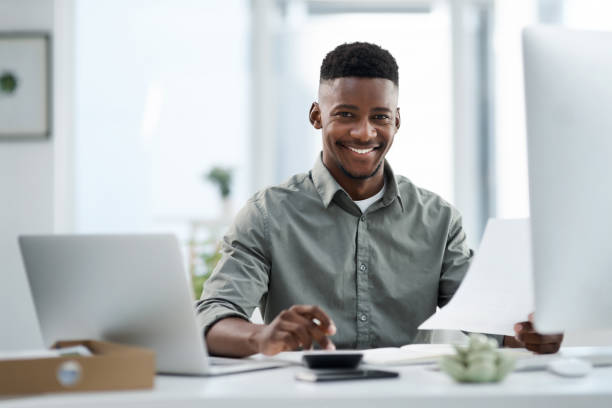 Shot of a young businessman working on a computer in an office stock photo