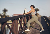 istock Shot of a young woman stretching on a footbridge 1313649150