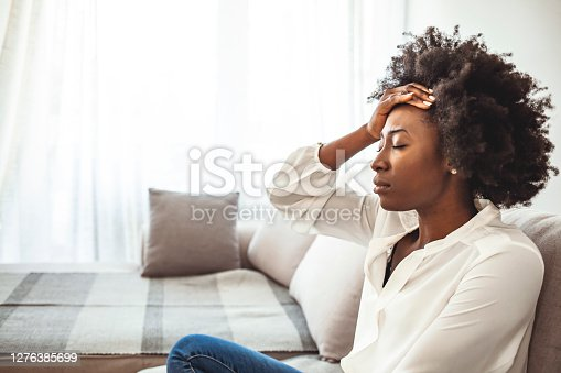 Lonely sad woman deep in thoughts sitting daydreaming or waiting for someone in the living room with a serious expression, she is pensive and suffering from insomnia sitting on couch