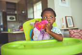 istock Shot of an adorable little girl holding her sippy cup while sitting in her feeding chair 1314972511