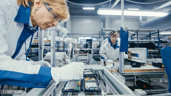 istock Shot of an Electronics Factory Workers Assembling Circuit Boards by Hand While it Stands on the Assembly Line. High Tech Factory Facility. 1145276223