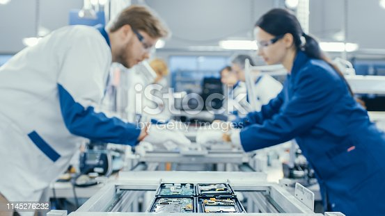 istock Shot of an Electronics Factory Workers Assembling Circuit Boards by Hand While it Stands on the Assembly Line. High Tech Factory Facility. 1145276232