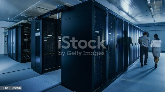 1131198396istockphoto Shot of an IT Admin with a Laptop Computer and Young Technician Colleague Walking Next to Server Racks in Data Center. Running Diagnostics or Maintenance. 1131198396