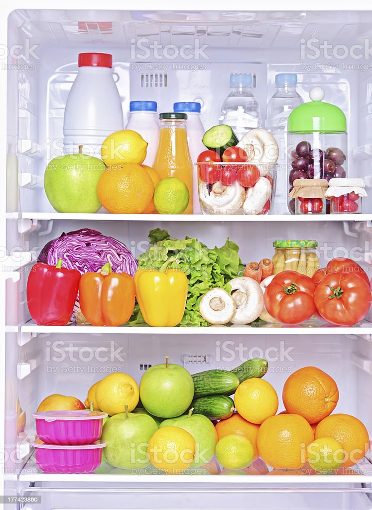 Shot of an open fridge with food products royalty-free stock photo
