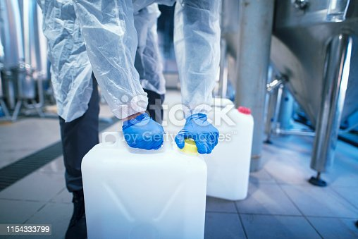 Industrial worker technologist working with chemicals in production plant.