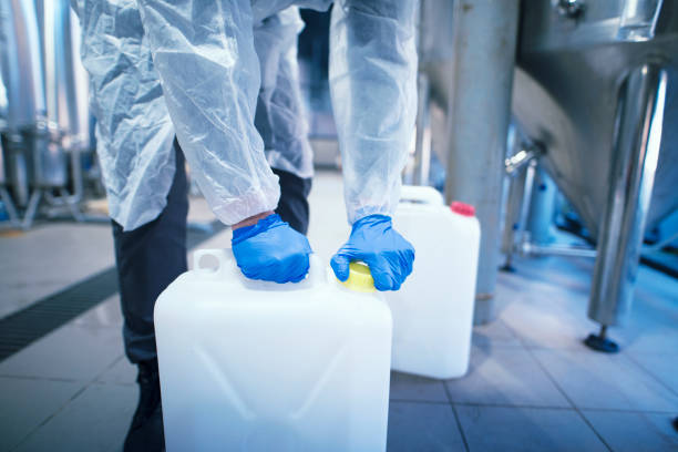 Shot of an unrecognizable industrial worker technologist with protective rubber gloves opening plastic can with chemicals in factory. Industrial worker technologist working with chemicals in production plant. hazardous chemicals stock pictures, royalty-free photos & images