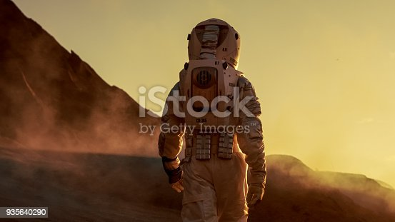 istock Shot of Astronaut Confidently Walking on Mars. Red Planet Covered in Gas and Smoke. Humans Overcoming Difficulties. Big Moment for the Human Race. 935640290