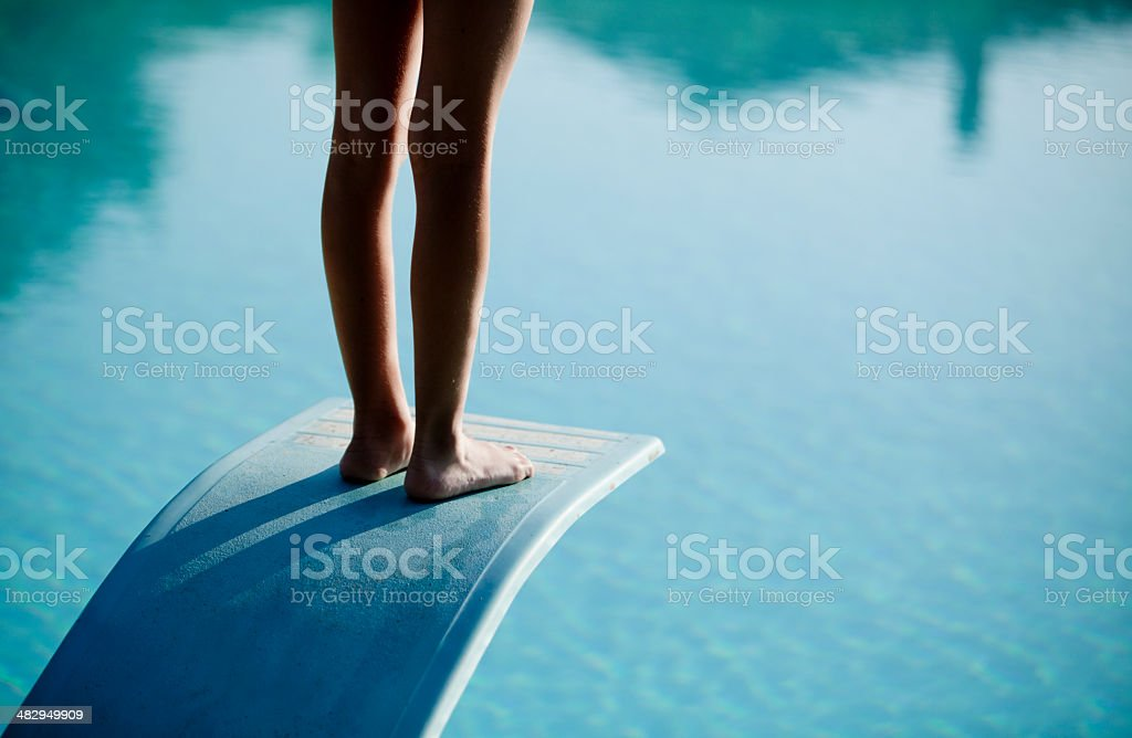 Shot of bare legs on diving board above blue water stock photo