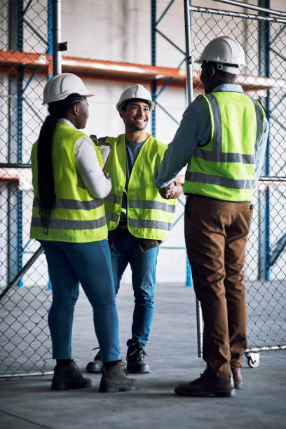 Shot of builders shaking hands at a construction site stock photo