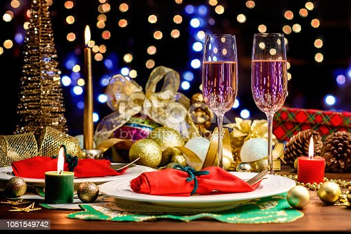 istock Shot of Champagne flutes in table for two over golden holiday background. Christmas and New Year celebration 1051549742