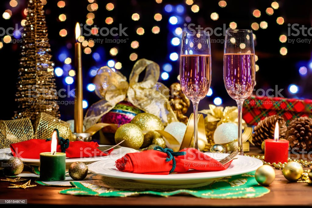 Shot of Champagne flutes in table for two over golden holiday background. Christmas and New Year celebration stock photo