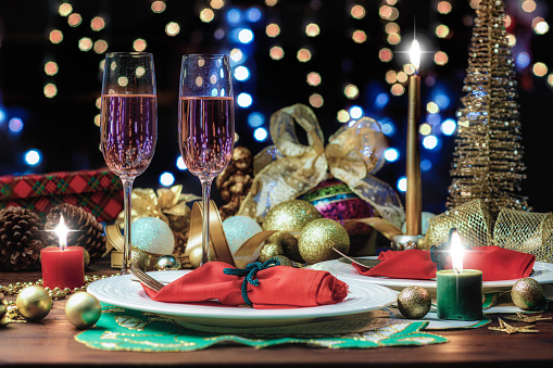Shot of Champagne flutes in table for two over golden holiday background. Christmas and New Year celebration