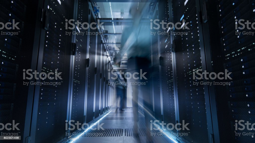 Shot of Corridor in Large Data Center Full of Moving and Working People. Pronounced Motion Blur. stock photo